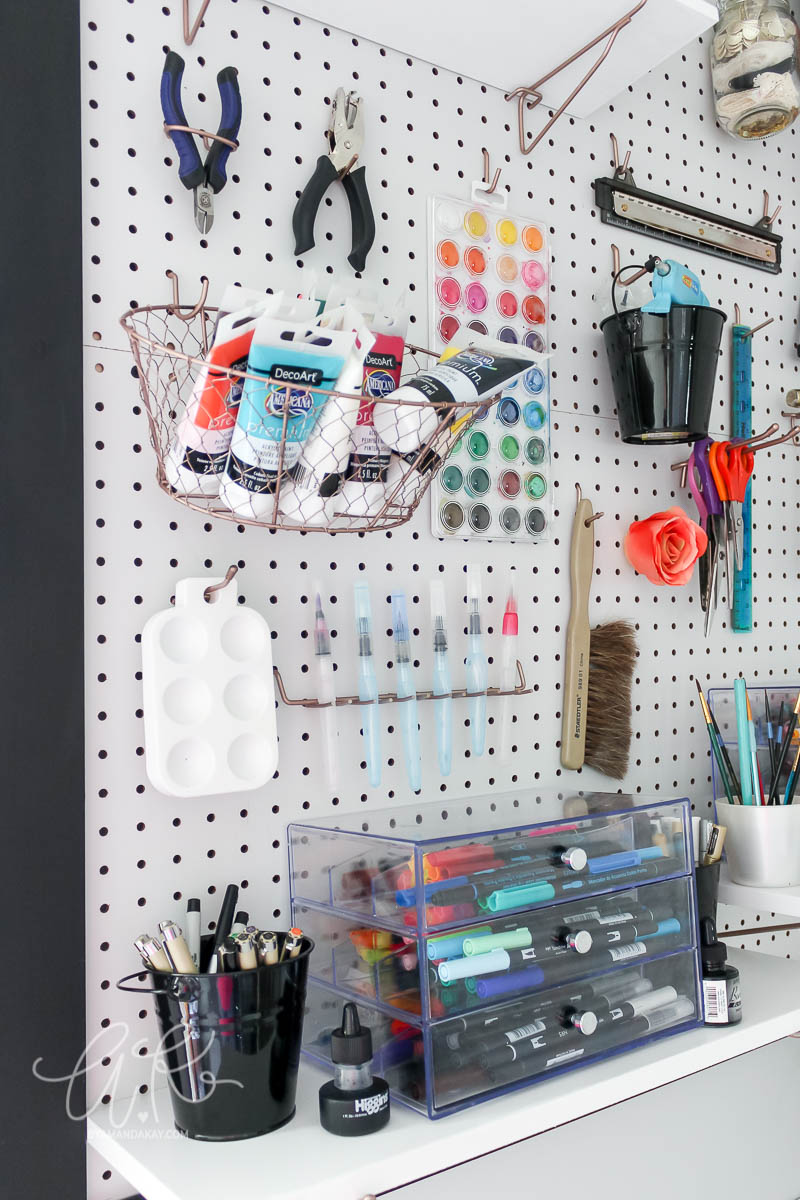 watercolor and brush storage on pegboard