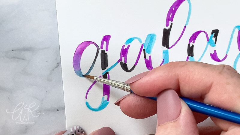 "close up blending colors together with a brush on the letter ""g"""