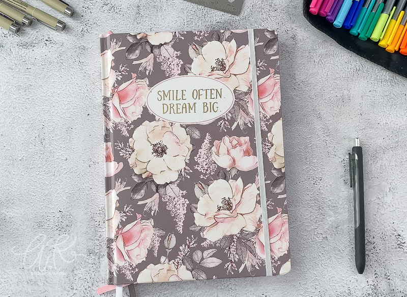 gray and pink hard cover floral notebook on table with pens