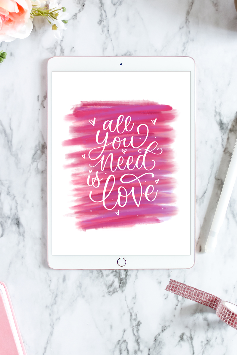 "Digital ""All you need is Love"" artwork on an ipad on a marble backdrop with flowers and washi tape"
