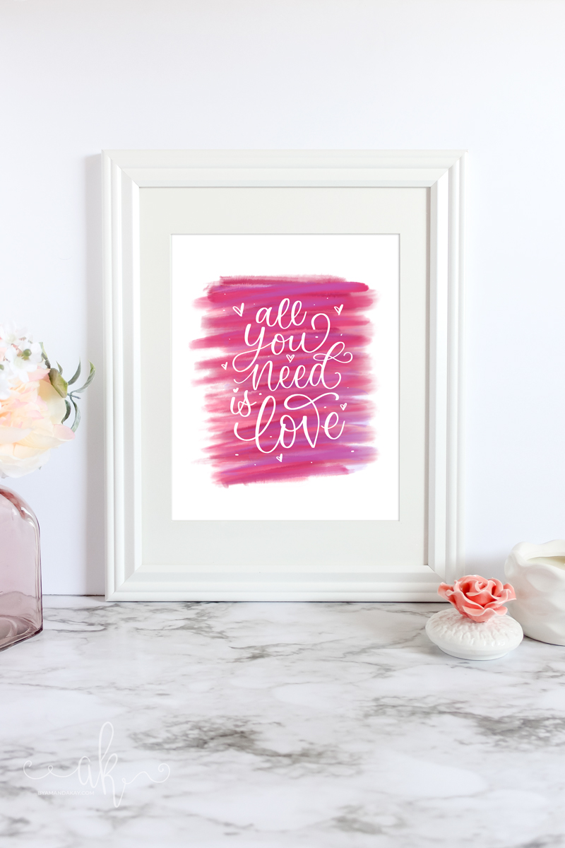 "Digital ""All you need is Love"" artwork inside a frame on marble table with candle and flowers"