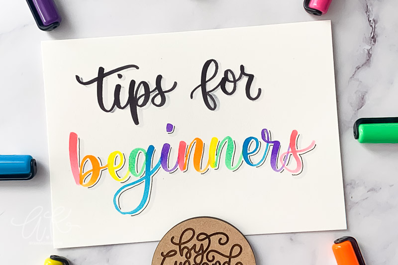 Zoomed in tips for beginners calligraphy on paper with bright colored markers.