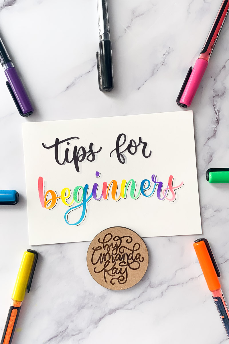tips for beginners calligraphy on paper with bright colored markers on a marble backdrop