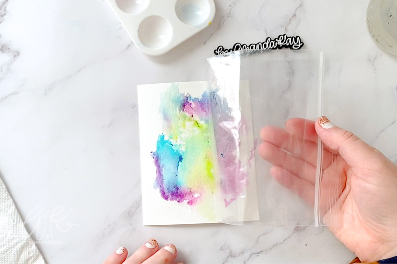 Peeling up the plastic bag from paper after watercolor smoosh.